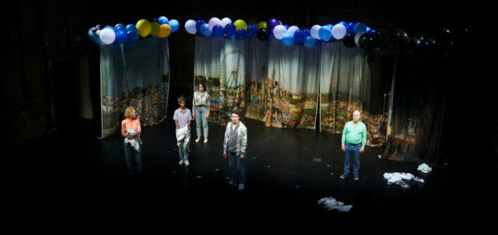 Fünf Schauspielende vor einem bedruckten Vorhang auf einer Bühne