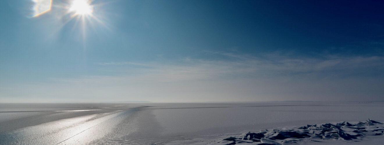 vereister See mit Schnee und blauem Himmel