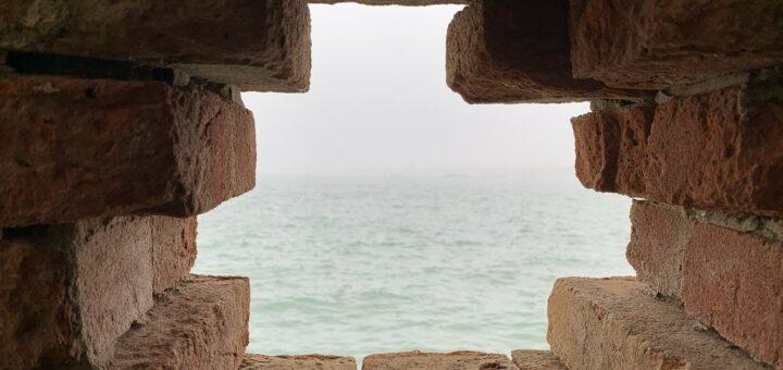 Blick durch ein Loch in einer Mauer auf das Meer