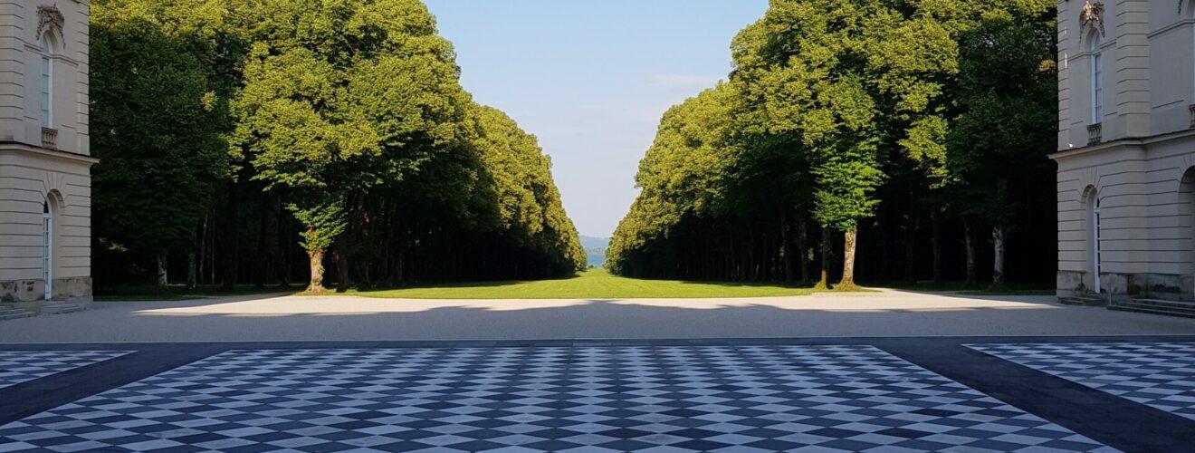 Schachbrettartiger Steinboden in der ersten Bildhälfte, sich öffnest zu einer Alle mit Bäumen und blauem Himmel