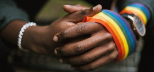 Hände mit Regenbogenband umwickelt