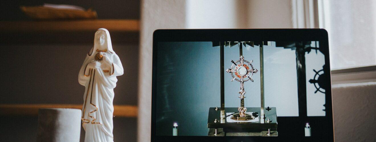 kleine Marienstatue neben einem Laptop auf dem ein Kreuz zu sehen ist
