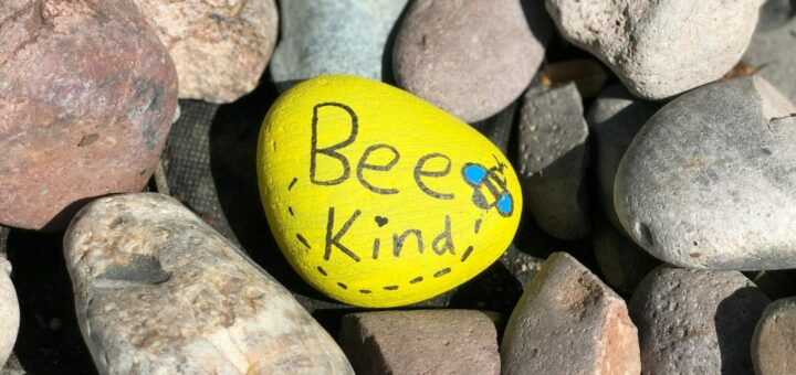 """faustgroße Steine von dem einer gelb bemalt ist und auf dem """"Bee kind"""" steht"""