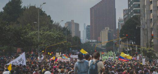 Demonstrierende Menschen auf einer breiten Straße mit kolumbianischer Flagge