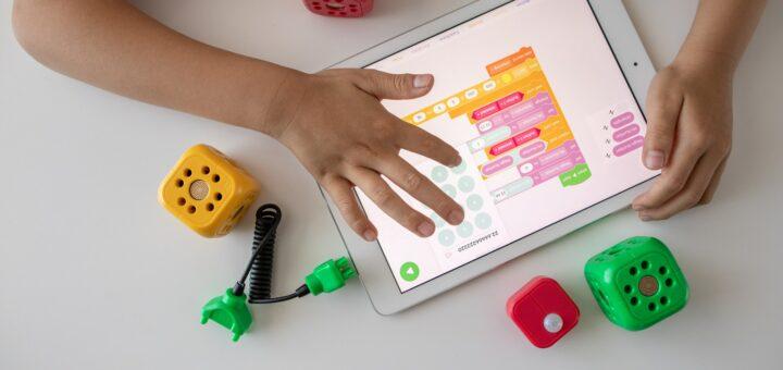 Ein Tablet auf dem Kinderhände und eine Aufgabe zu sehen sind und Spielzeug liegt daneben