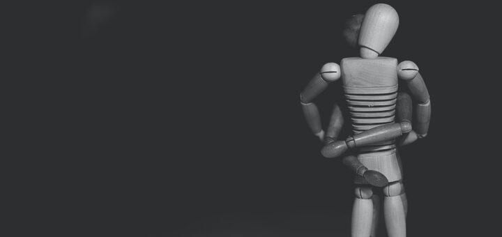 Zwei Holzfiguren umarmen sich.