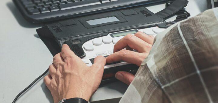 Auf einem weißen Tisch liegt eine schwarze Tastatur und darunter sieht man einen Screen Reader. Hände bedienen diesen.